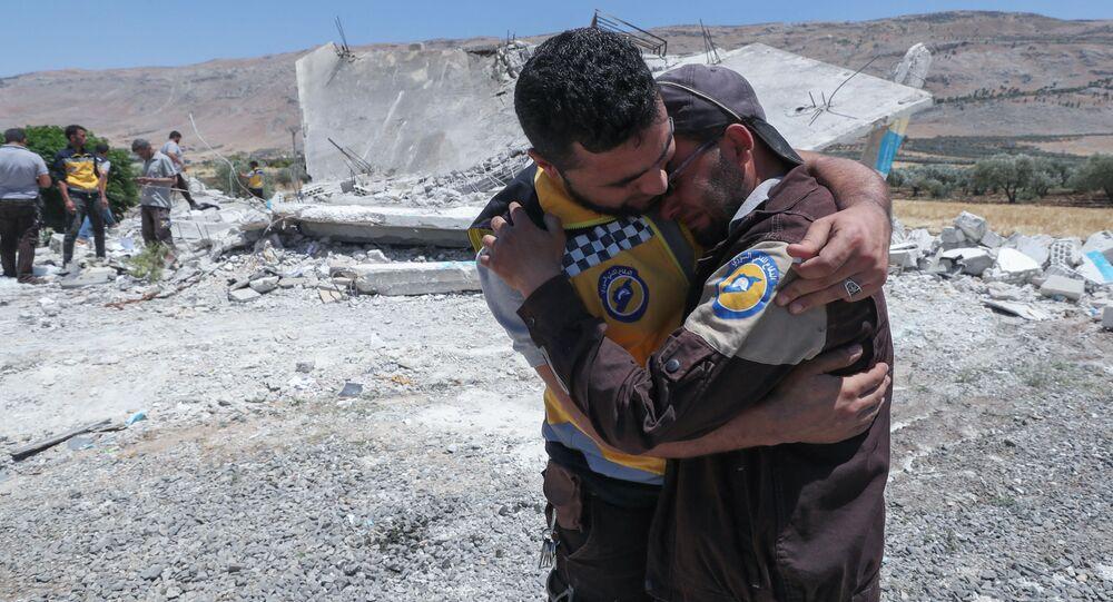 Membros do grupo pseudo-humanitário Capacetes Brancos lamentam a morte de um colega em bombardeio que atingiu a província de Hama, Síria, em 19 de junho de 2021