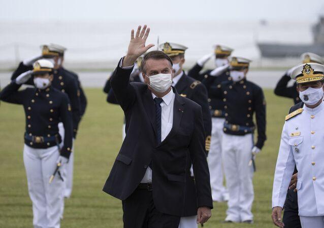 Presidente Jair Bolsonaro saúda pessoas durante cerimônia de graduação na Academia Naval, Rio de Janeiro, 19 de junho de 2021
