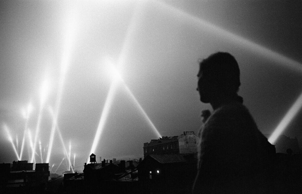 Feixes de luz projetados pelos sistemas de defesa antiaérea iluminam o céu de Moscou em junho de 1941