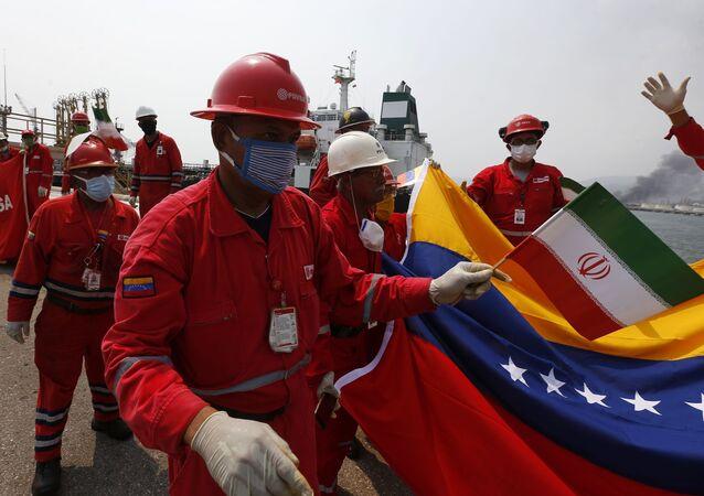 Trabalhador petrolífero da Venezuela com pequena bandeira do Irã participa de cerimônia de chegada do petroleiro iraniano Fortune na refinaria El Palito, perto de Puerto Cabello, Venezuela, 25 de maio de 2020