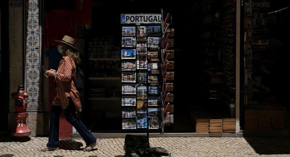 Mulher passa por loja de souvenir na Baixa de Lisboa, em 23 de junho de 2021