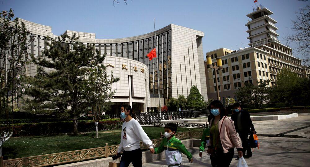 Pessoas usando máscaras faciais passam pela sede do Banco Popular da China, o banco central do país, 4 de abril de 2020