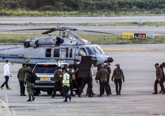 Presidente da Colômbia Iván Duque rodeado por guarda-costas perto do helicóptero presidencial que foi alvo de ataque no nordeste do país