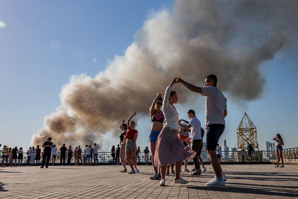 Pessoas dançam samba enquanto fumaça sobe de depósito pirotécnico em chamas em Moscou, Rússia, 19 de junho de 2021