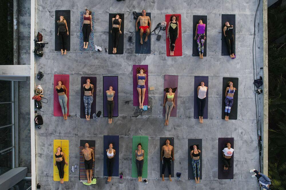 Praticantes de yoga mantêm distanciamento social durante a pandemia da COVID-19, no telhado do Estúdio ARA Yoga Caracas, em Caracas, Venezuela, Dia Internacional do Yoga, 21 de junho de 2021