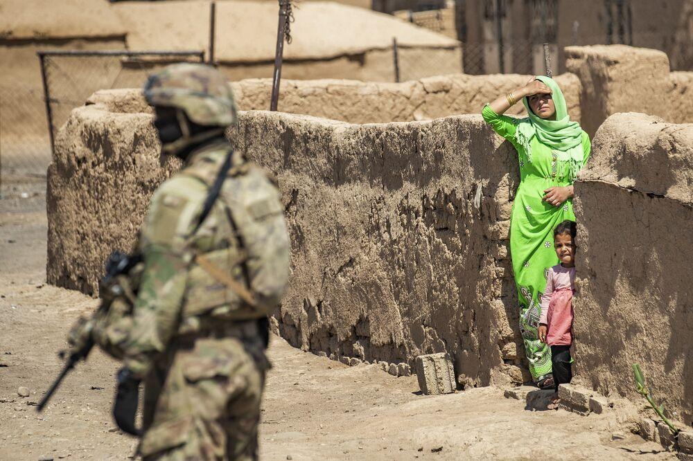 Soldado dos EUA perto de mulher e criança durante patrulha militar em Rumeilan, província de Al-Hasakah, Síria, 22 de junho de 2021