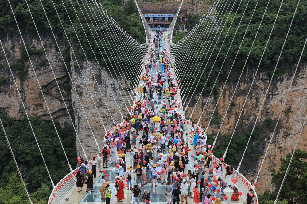 Foto aérea mostra pessoas caminhando em ponte de Zhangjiajie, província de Hunan, China, 20 de junho de 2021