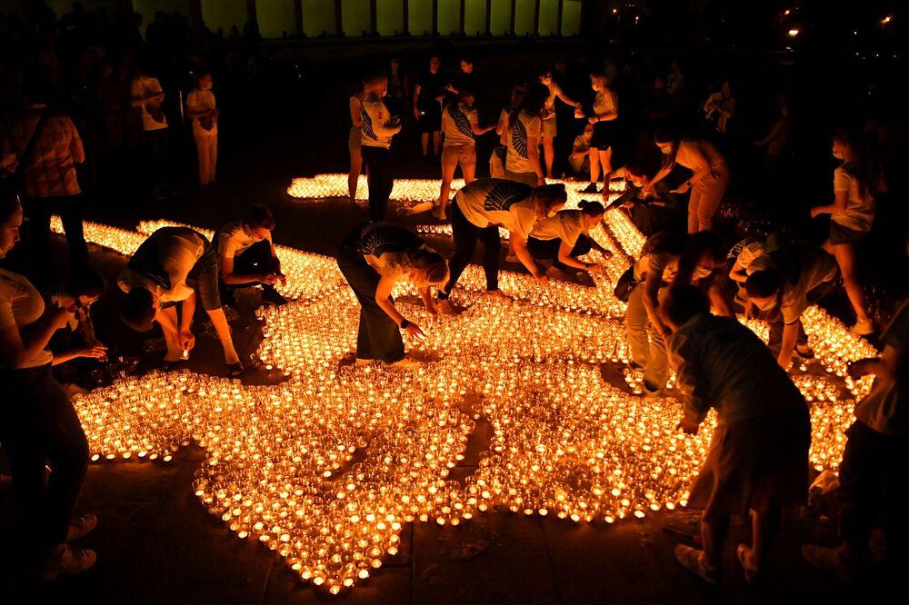 Participantes da ação Vela da Memória acendem velas em frente ao Museu da Vitória em Moscou, Rússia, na noite de 22 de junho, dia que comemora 80º aniversário do início da Grande Guerra pela Pátria no país