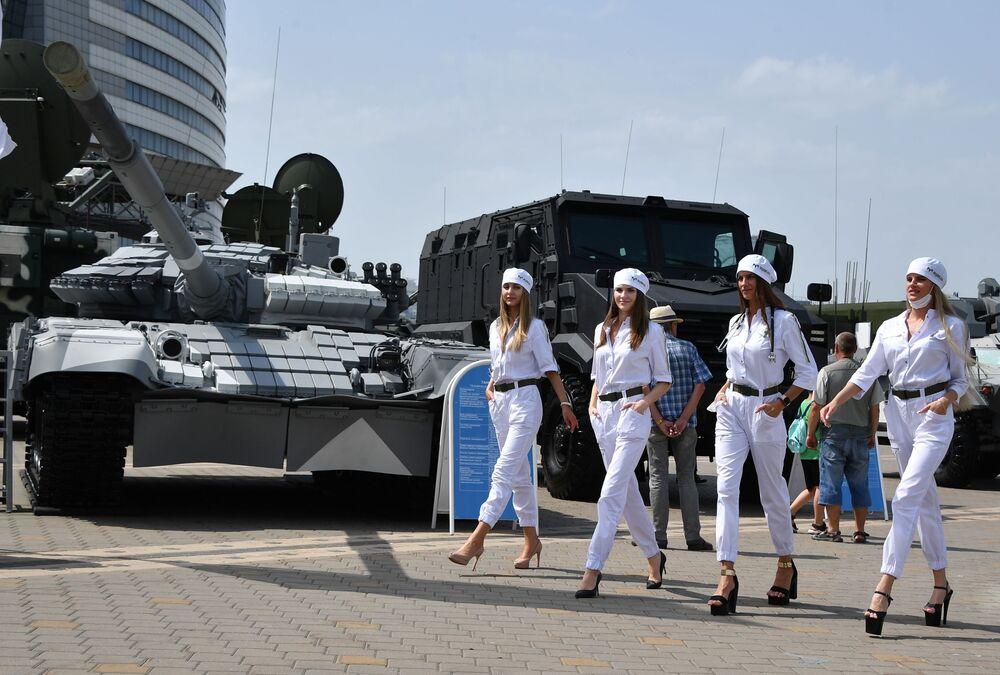 Mulheres junto de veículos militares na 10ª Exposição Internacional de Armas e Equipamentos Militares MILEX-2021 em Minsk, Belarus, 23 de junho de 2021