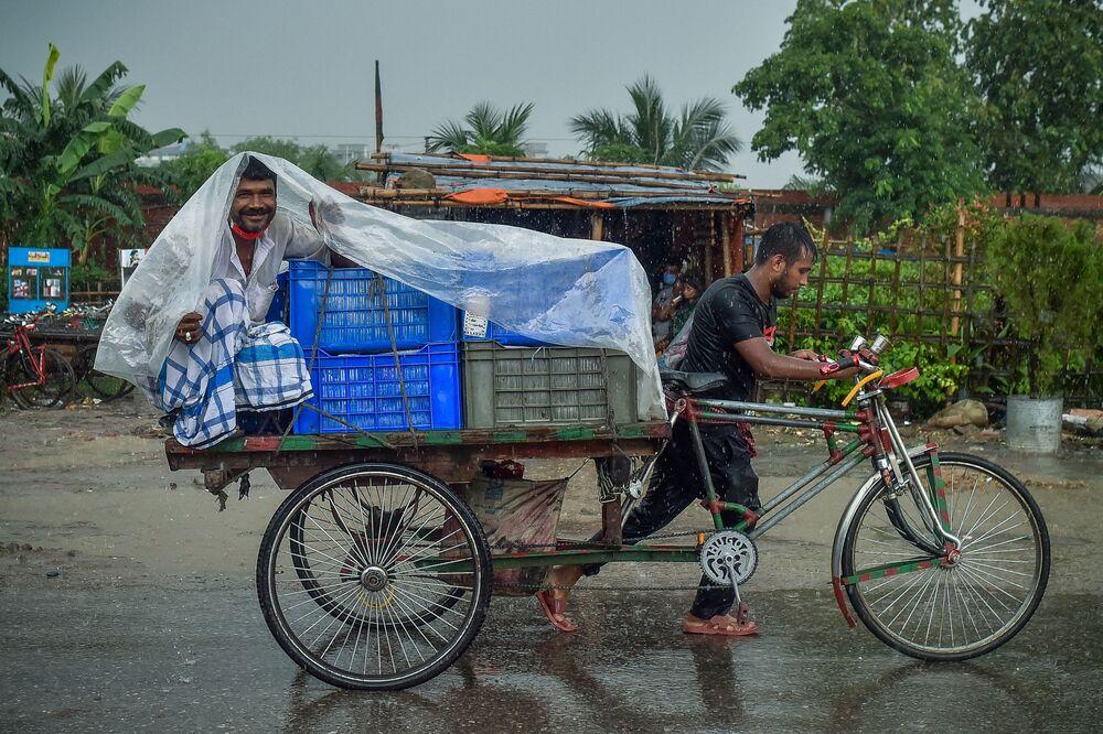 Homem em riquixá se abriga da chuva em Daca, Bangladesh, 21 de junho de 2021