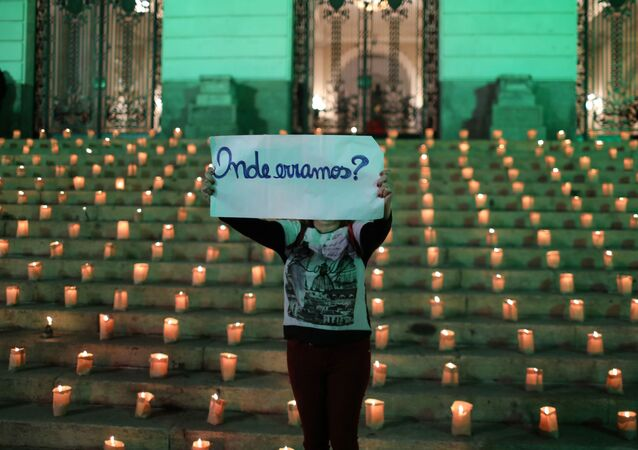 Mulher segura placa durante evento em homenagem às 500.000 pessoas que morreram da doença do novo coronavírus (COVID-19) no Brasil, Rio de Janeiro, Brasil, 21 de junho de 2021