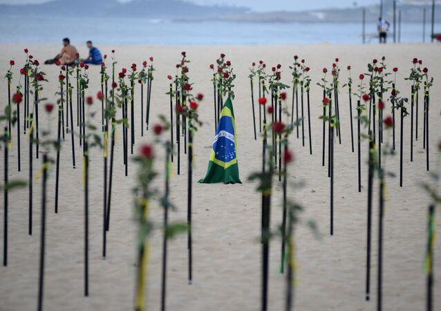 Bandeira do Brasil em meio a flores vermelhas colocadas pela ONG Rio de Paz na praia de Copacabana para homenagear a morte de 500.000 pessoas pela COVID-19 no Rio de Janeiro, Brasil, 20 de junho de 2021