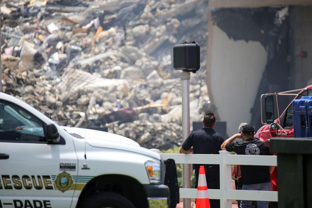 Socorristas olham para os escombros do edifício residencial, enquanto as equipes de emergência continuam as operações de busca e resgate de sobreviventes em Surfside, perto de Miami Beach, Flórida, EUA, 26 de junho de 2021