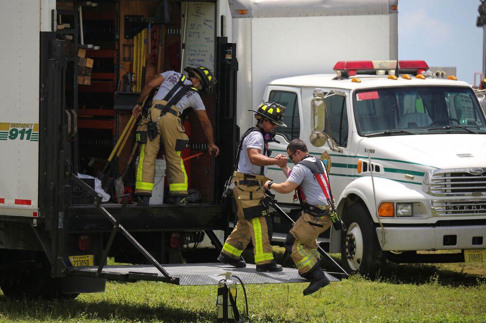 Membros da Equipe de Resgate dos Bombeiros de Miami-Dade no lugar do colapso do edifício residencial em Surfside, Flórida, Estados Unidos, 26 de junho de 2021