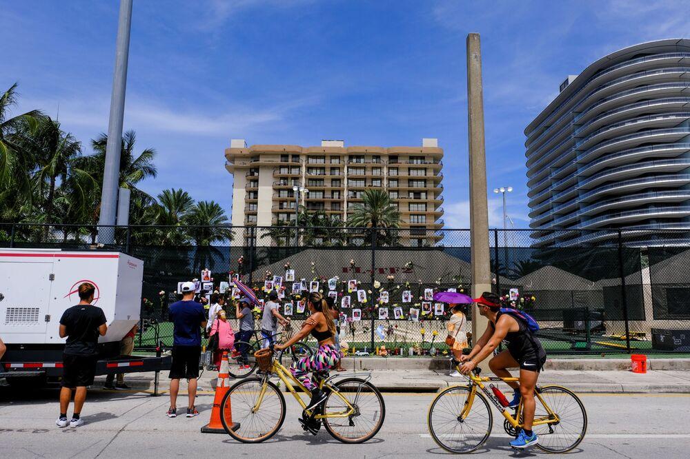 Pessoas olham para o espaço memorial criado por vizinhos em frente do edifício parcialmente destruído em Surfside, perto de Miami Beach, Flórida, EUA, 26 de junho de 2021