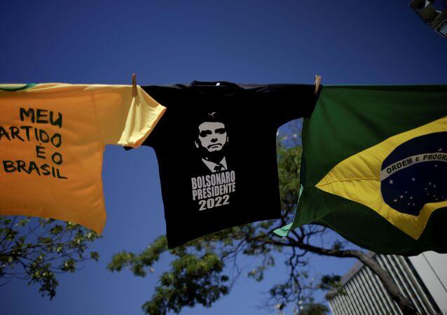 Bandeira brasileira e camisetas com imagens de Jair Bolsonaro durante manifestação em apoio do presidente, 27 de junho de 2021