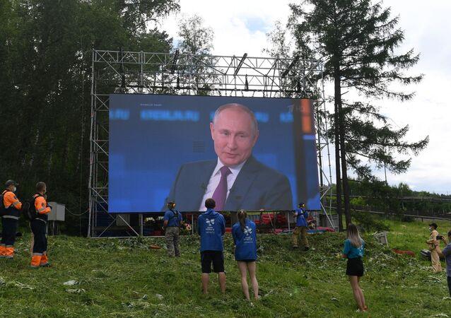 Pessoas assistindo à Linha Direta com Putin na região de Krasnoyarsk