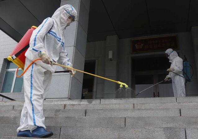 Funcionários de uma escola primária de Pyongyang, na Coreia do Norte, usando spray desinfetante como uma das medidas de combate ao novo coronavírus, em 30 de junho de 2021