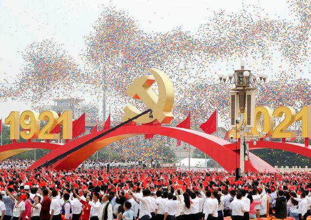 Participantes com bandeiras nacionais saúdam libertação de balões no fim do evento marcando o centenário da fundação do Partido Comunista da China, Pequim, China, 1º de julho de 2021