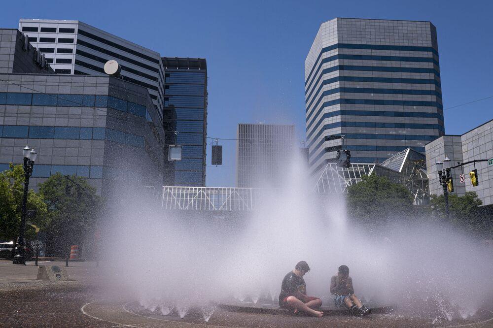 Crianças brincam em fonte de Portland, estado do Oregon, EUA, 27 de junho de 2021