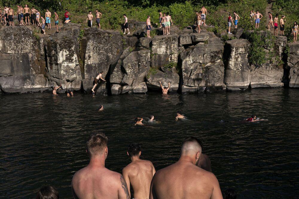 Adeptos de salto e mergulho no rio Clackamas, no parque High Rocks em Portland, estado do Oregon, EUA, 27 de junho de 2021