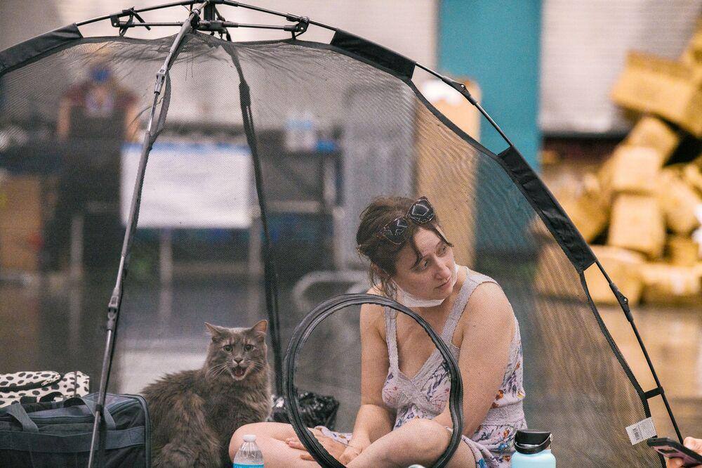 Mulher e seu gato descansam dentro de uma tenda na estação de resfriamento em Oregon, EUA, 28 de junho de 2021