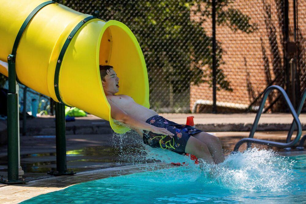 Menino no escorrega d'água na piscina pública durante calor anormal em Portland, EUA, 27 de junho de 2021