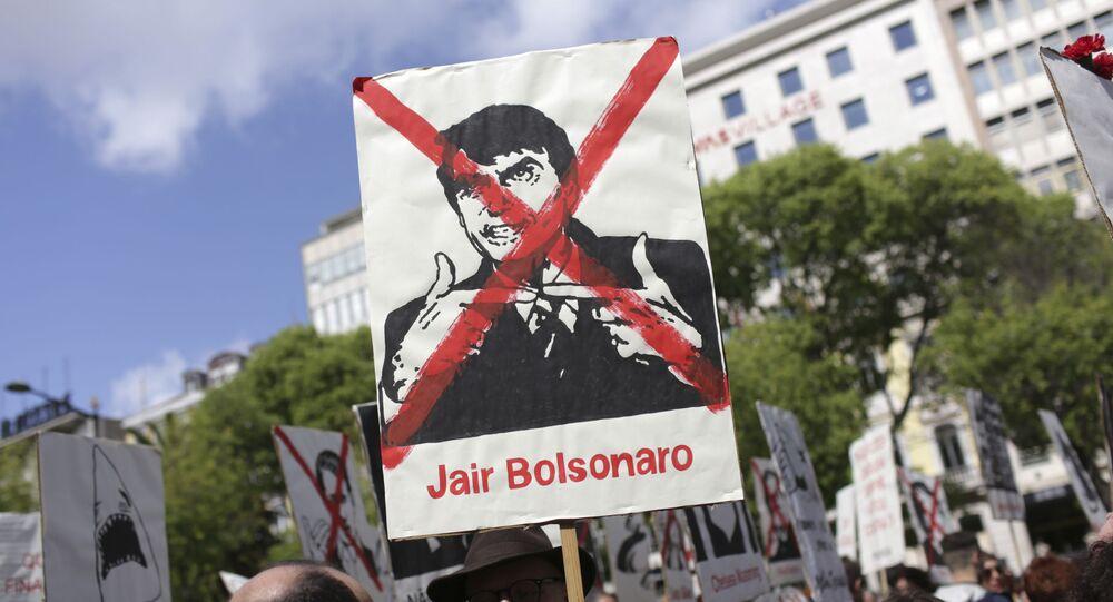 Manifestante segura cartaz contra Bolsonaro no Desfile de 25 de Abril, em 2019, em Lisboa