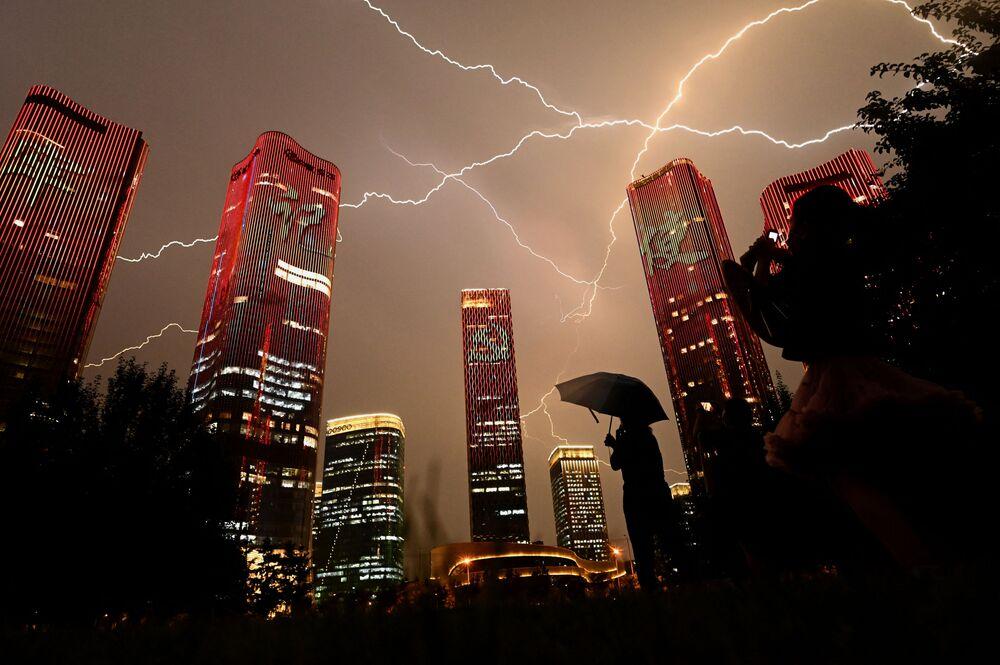 Raio atravessa o céu enquanto pessoas observam um espetáculo de luzes na véspera do 100º aniversário do Partido Comunista da China em Pequim, China, 30 de junho de 2021