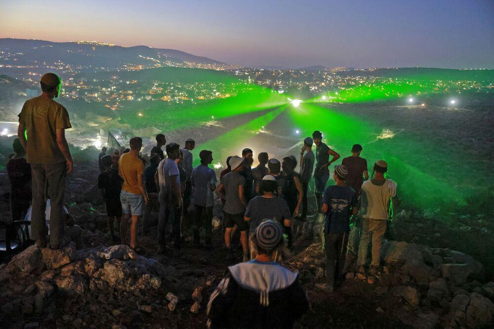 Colonos e apoiadores israelenses no recém-criado posto avançado de Eviatar observam manifestantes palestinos apontando raios laser em sua direção a partir da aldeia vizinha de Beita, perto da cidade palestina de Nablus, Cisjordânia ocupada, 28 de junho de 2021