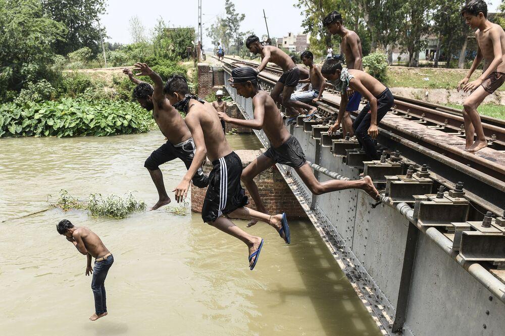 Jovens saltam em canal para se refrescar durante dia quente de verão na periferia de Amritsar, Índia, 27 de junho de 2021