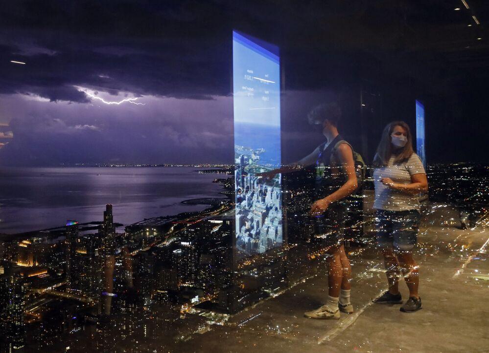 Pessoas refletidas em parede de vidro da Torre Willis em meio a tempestade perto do lago Michigan, Chicago, EUA, 29 de junho de 2021