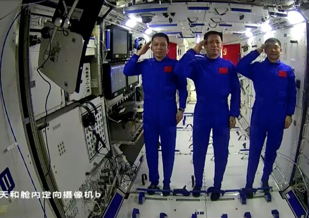Astronautas chineses Nie Haisheng, Liu Boming e Tang Hongbo da missão Shenzhou-12 enquanto falam com o presidente chinês Xi Jinping no módulo principal Tianhe da estação espacial em construção Tiangong, 23 de junho de 2021