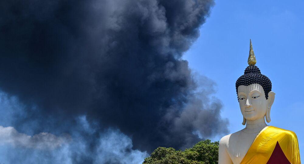 Fumaça tóxica de explosão e incêndio em uma fábrica localizada próximo de Bangkok é vista atrás da estátua de Buda, na Tailândia