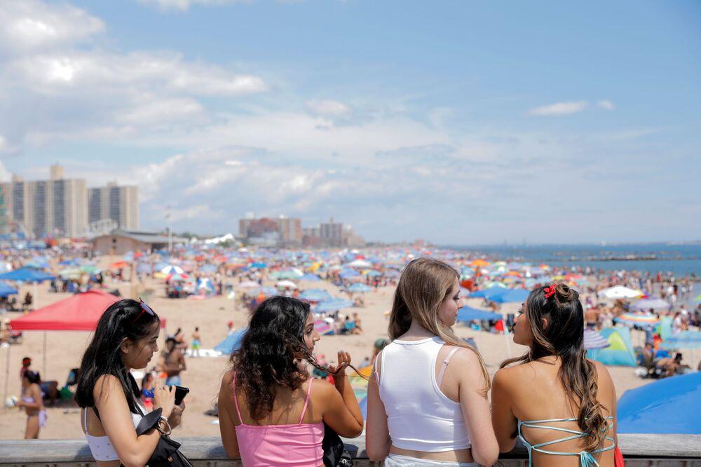 Meninas olham para a praia de Coney Island durante festa do Dia da Independência em Nova York, EUA, 4 de julho de 2021