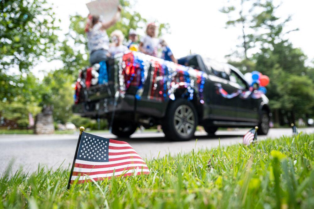 Bandeira dos EUA em frente de veículo decorado durante o desfile comemorativo do Dia da Independência dos EUA no Kentucky, 4 de julho de 2021
