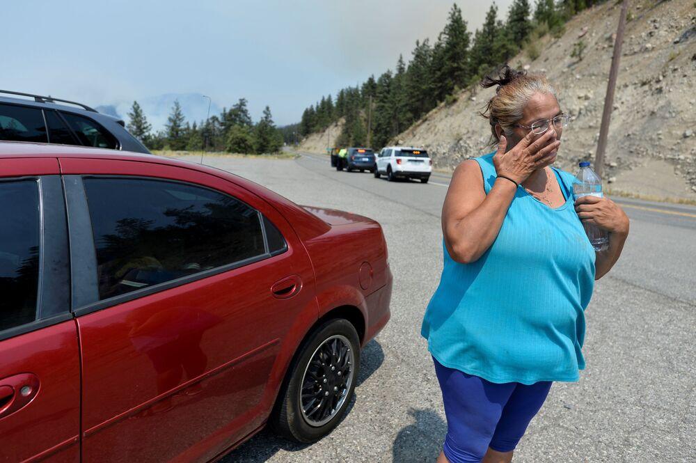 Mulher residente na vila de Lytton ao lado de seu carro após o incêndio ter atingido a vila, forçando seus moradores a abandonar suas casas, Canadá, 1º de julho de 2021