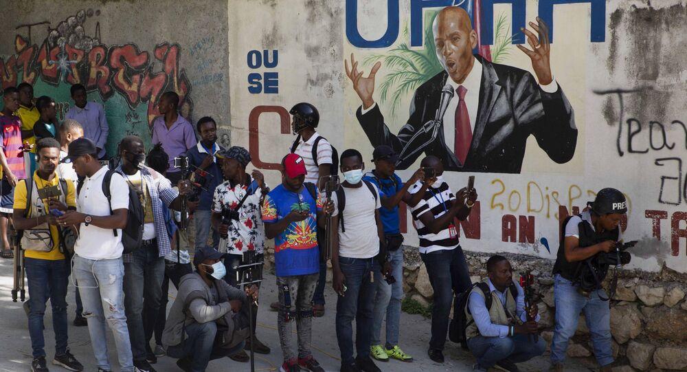 Jornalistas ao lado de mural com imagem do presidente do Haiti, Jovenel Moïse, perto da residência onde ele foi assassinado, Haiti, 7 de julho de 2021