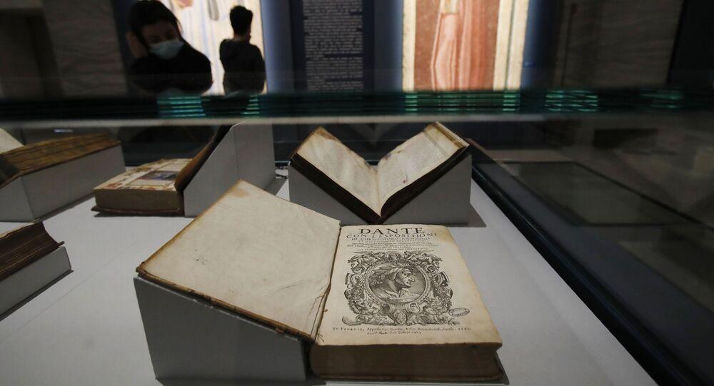 Mulher olha para livros antigos em exposição de obras de Dante Alighieri em Forli, Itália, 8 de maio de 2021