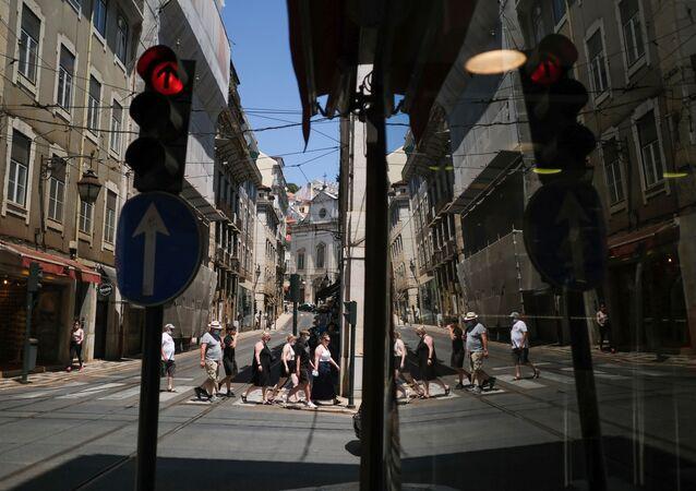 Sinal vermelho: pessoas com máscara de proteção andam pela Baixa de Lisboa, em 8 de julho de 2021