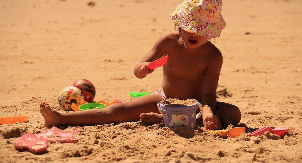 Criança brincando na areia (imagem referencial)