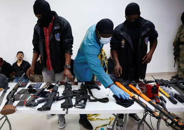 Armas, telefones celulares, passaportes e outros itens estão sendo mostrados à mídia junto com os suspeitos do assassinato do presidente Jovenel Moïse, que foi morto a tiros na manhã de quarta-feira em sua casa, em Port-au-Prince, Haiti, 8 de julho de 2021