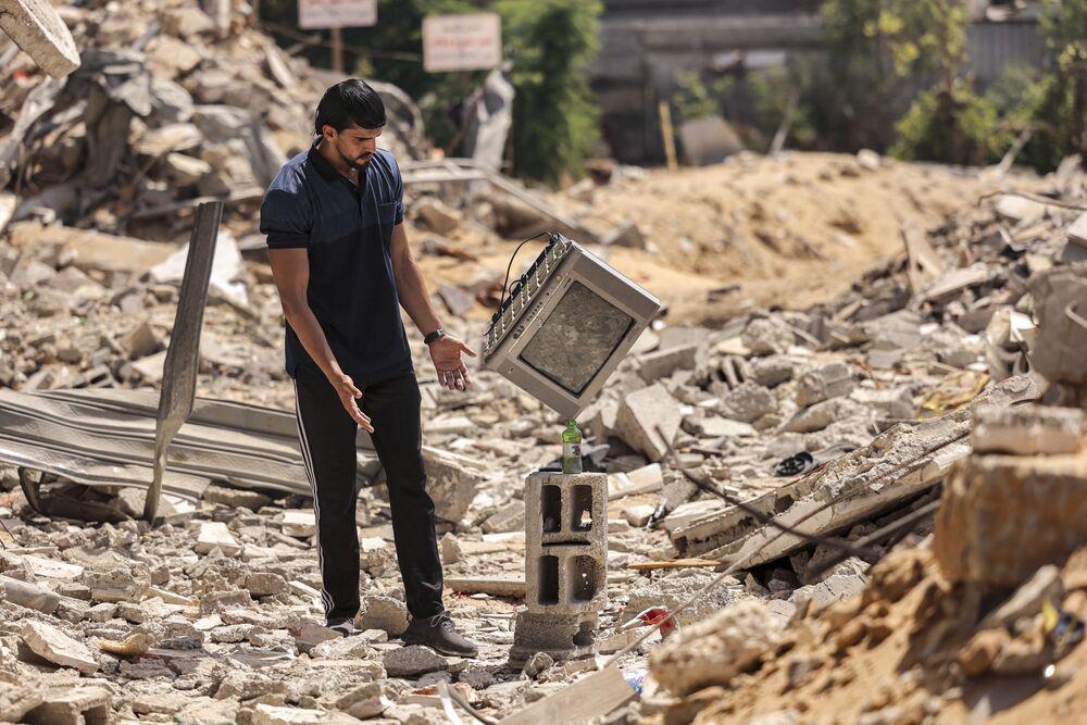 Artista de performance palestino Mohammed al-Shenbari ajusta uma televisão em cima de garrafa colocada em escombros demonstrando sua habilidade em equilibrar objetos