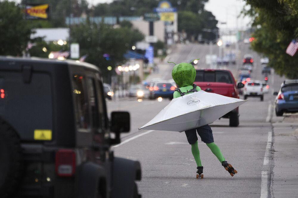 Homem em traje alienígena em disco voador patinando na rua durante o festival de OVNIs em Roswell, Novo México, EUA