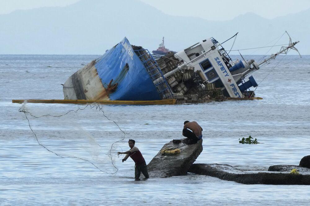Pescador lança rede de pesca perto de um navio meio submerso na baía de Manila, Filipinas