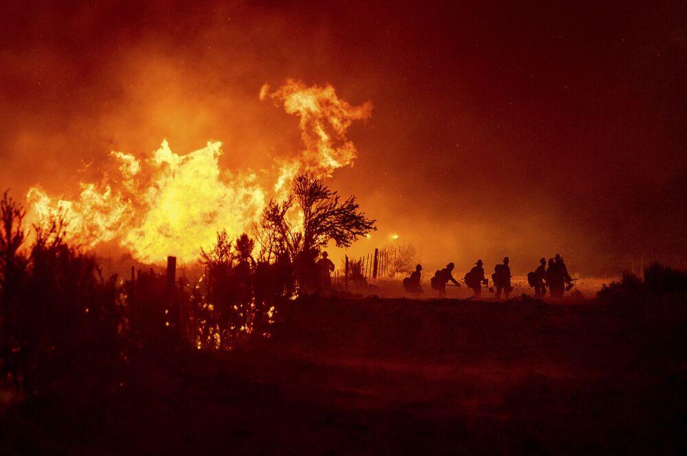 Bombeiros combatem incêndio, em Doyle, norte da Califórnia, EUA, 9 de julho de 2021