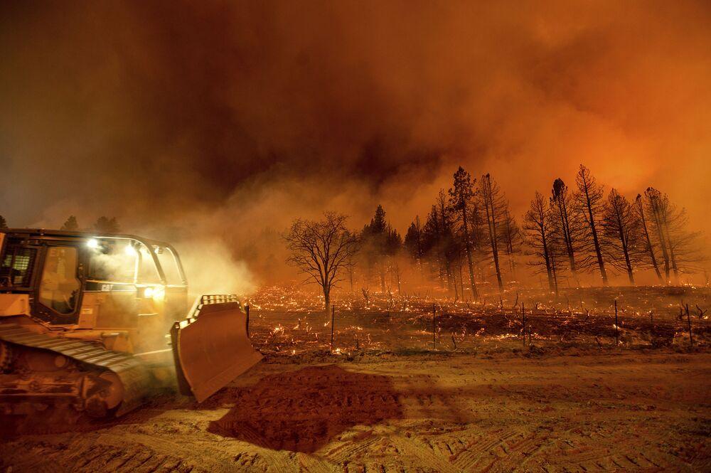 Trator de esteira passa por campo em chamas, norte da Califórnia, EUA, 9 de julho de 2021