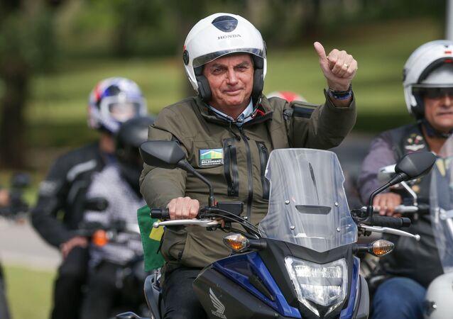 Presidente Jair Bolsonaro (na moto azul, na frente do grupo) participa de passeio de moto pelas ruas de Brasilia, em Brasília (DF). Foto de arquivo