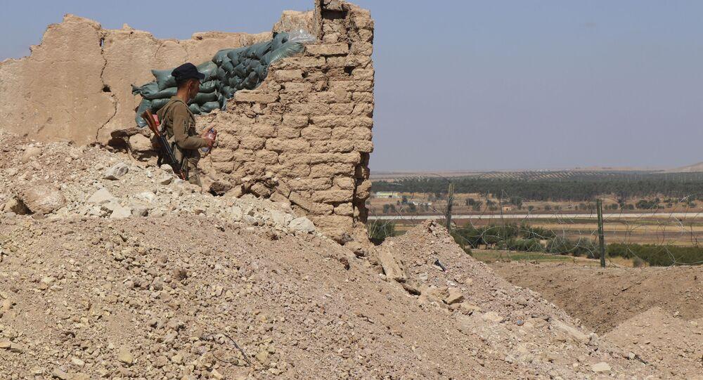 Combatente das Forças Democráticas da Síria (SDF, na sigla em inglês) dentro de posto em que antes estavam militares dos EUA, na cidade de Tal Abyad, fronteira sírio-turca, Síria, 7 de outubro de 2019