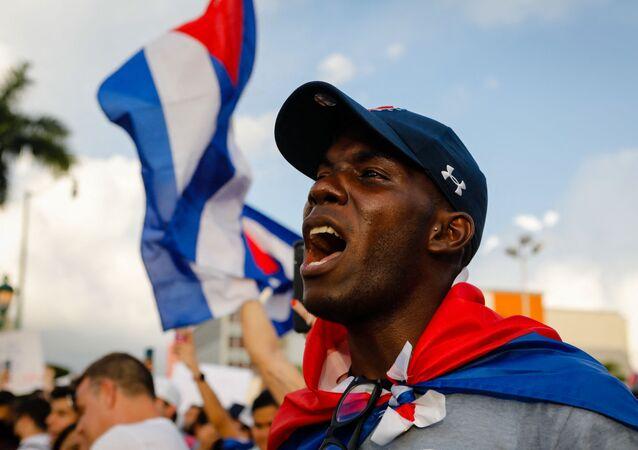 Homem entoa cântico durante manifestações em Cuba contra o governo do país, Miami, 11 de julho de 2021